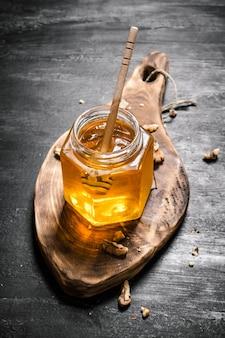 Fond de miel. un pot de miel frais avec des noix sur le plateau. sur table rustique noire.