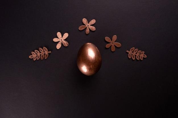 Fond minimal de pâques avec des oeufs de pâques en or sur fond noir. mise à plat, vue de dessus, espace copie.