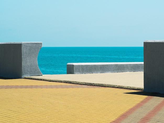 Fond minimaliste avec mer, murs blancs et fond de trottoir jaune