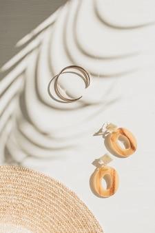 Fond de mode avec des accessoires pour femmes sur un tableau blanc avec une ombre de feuille. mise à plat, vue de dessus.