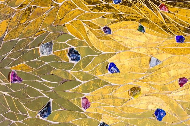 Fond de mosaïque dorée ornée de pierres colorées.