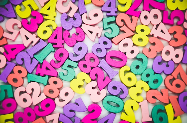 Fond multicolore lumineux de nombres en bois de zéro à neuf. vue de dessus, texture colorée abstraite avec des nombres. concept: retour à l'école, maths.