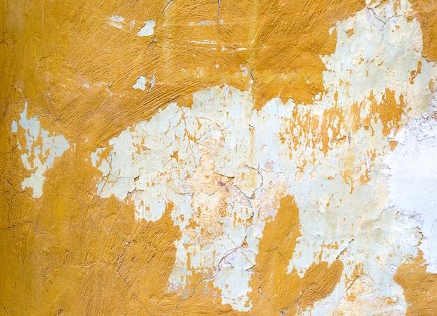 Fond de mur de béton peint jaune fissuré