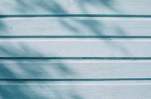 Fond de mur en bois bleu avec des ombres de branches d'arbres.