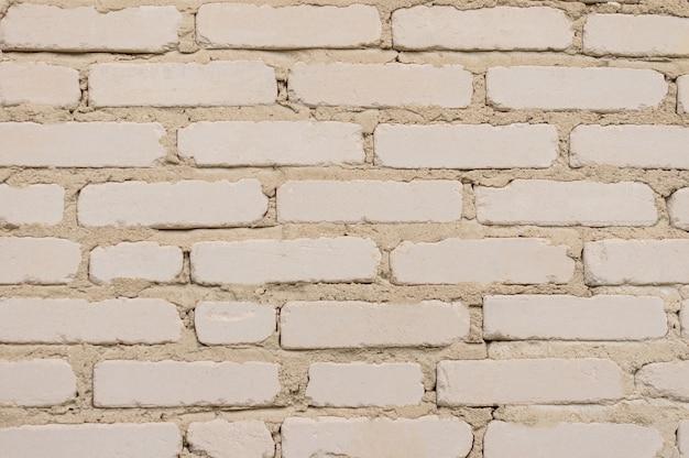 Fond de mur de brique ancienne teinté blanc patiné.