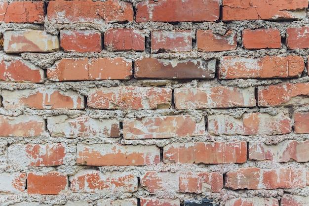 Fond de mur de briques anciennes taché par les intempéries.