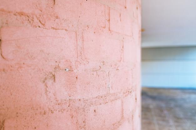 Fond d'un mur de briques ondulées avec des tons de rose tendre.