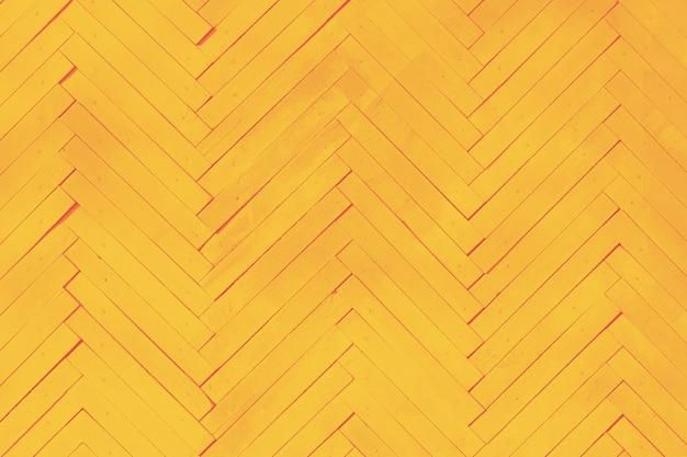 Fond de mur jaune de planches de bois disposées en os de hareng