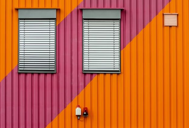 Fond d'un mur en métal orange et violet avec des oeillères de fenêtre blanches