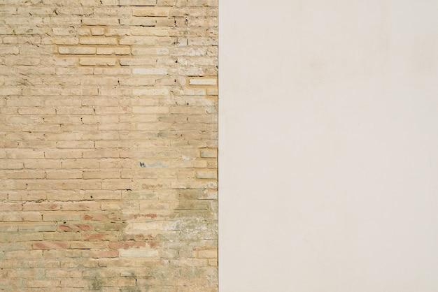 Fond d'un mur moitié blanc et moitié avec des briques, divisé en deux moitiés.