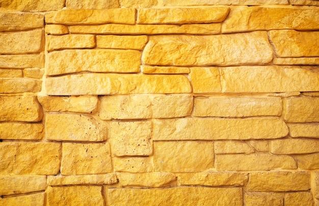 Fond de mur de pierre dorée. fond de mur de briques.