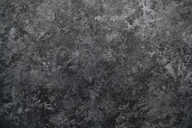 Fond de mur en pierre noir foncé avec surface texturée.