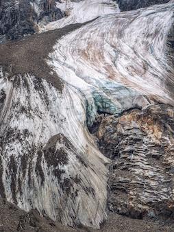 Fond de nature de la surface sombre du glacier avec des fissures et des rayures. toile de fond naturelle minimale de mur de glace et de blocs de glace du glacier en gros plan. belle texture de la nature du mur glaciaire.