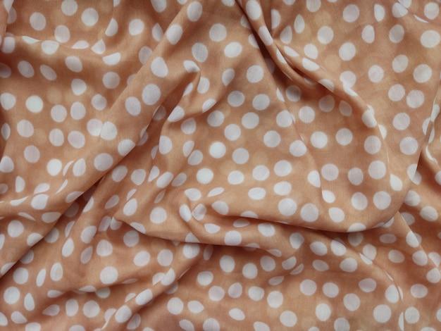 Fond naturel délicat beige pour les cosmétiques et le tissu de beauté textile à la mode parsemé de perles blanches et de parfum avec des feuilles vertes nature et beauté féminité