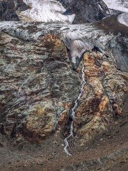 Fond naturel minimaliste du ruisseau qui coule à la surface du glacier. fond naturel minimal du mur de glace. belle texture naturelle d'un mur glaciaire sombre avec des ruisseaux d'eau. vue verticale