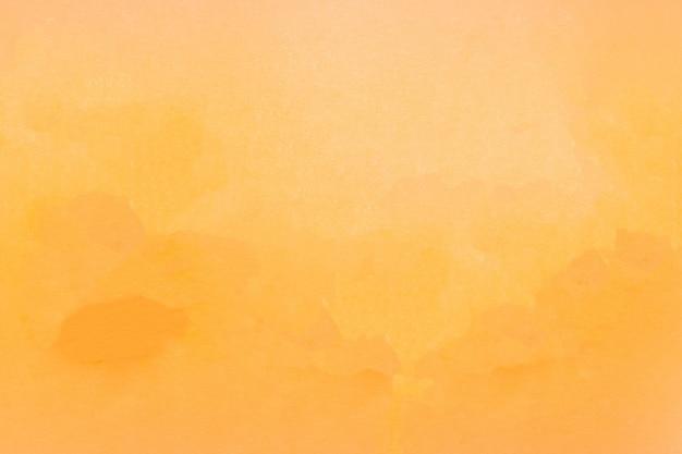 Fond naturel de papier texturé orange jaune.