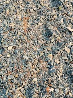 Fond naturel de petits cailloux de pierres, de sable et de branches naturelles, cadre vertical.