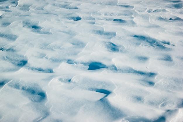 Fond neigeux blanc d'hiver avec des congères de neige fraîche.