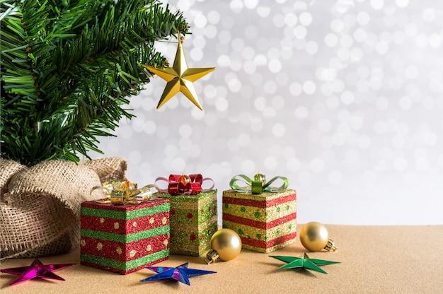 Fond de noël arbre de noël, boules dorées et coffrets cadeaux.