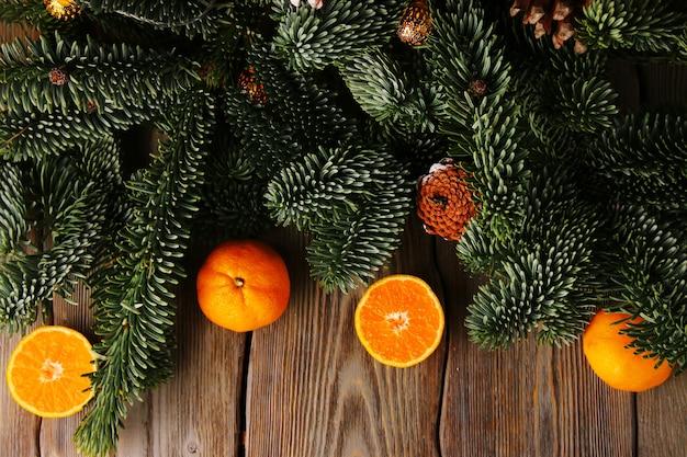 Fond de noël. arbre de noël et mandarine ou mandarine sur table en bois.