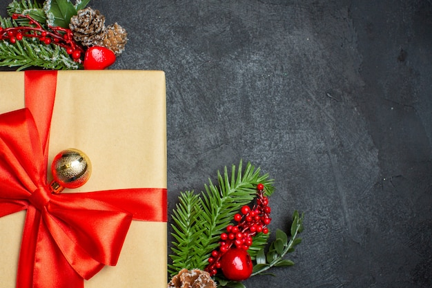 Fond de noël avec de beaux cadeaux avec ruban en forme d'arc et accessoires de décoration de branches de sapin sur une table sombre à moitié photo