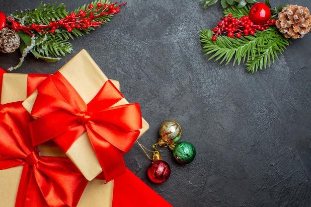 Fond de noël avec de beaux cadeaux avec ruban en forme d'arc et accessoires de décoration de branches de sapin sur une table sombre