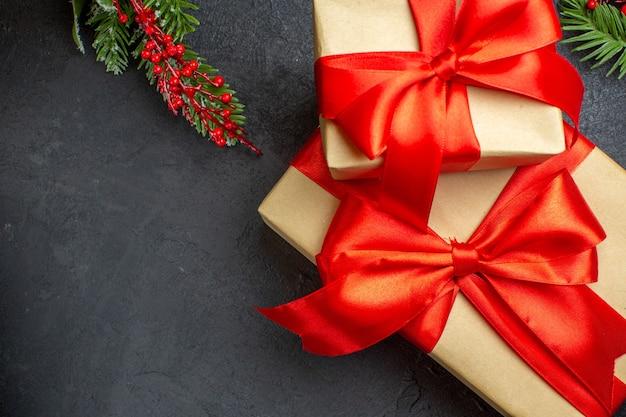 Fond de noël avec de beaux cadeaux avec ruban en forme d'arc et branches de sapin sur une table sombre