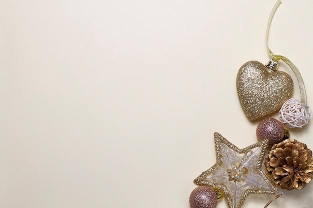 Fond de noël beige élégant avec des jouets dorés, des feuilles, des étoiles et des ballons.