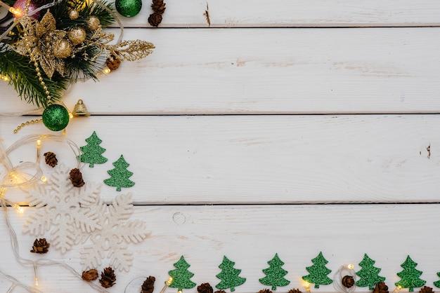 Fond de noël blanc décoré de décor de fête, lanternes, flocons de neige et branches d'arbres de noël