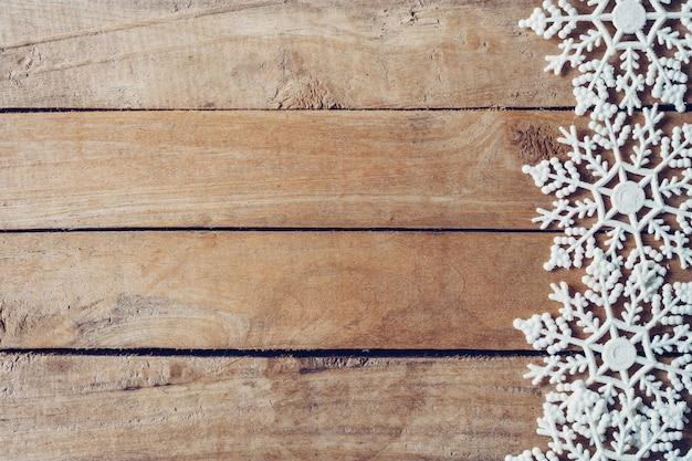 Fond de noël en bois marron avec des flocons de neige et décoration de noël.