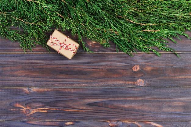 Fond de noël en bois noir. rameaux de thuya. carte florale originale et fraîche pour noël.