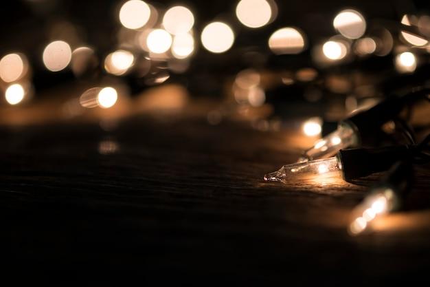 Fond de noël - bois vintage en planches avec des lumières et un espace de texte libre.
