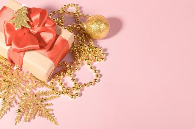 Fond de noël avec boîte-cadeau enveloppé dans du papier kraft recyclé avec noeud de ruban rouge et décoration dorée festive.