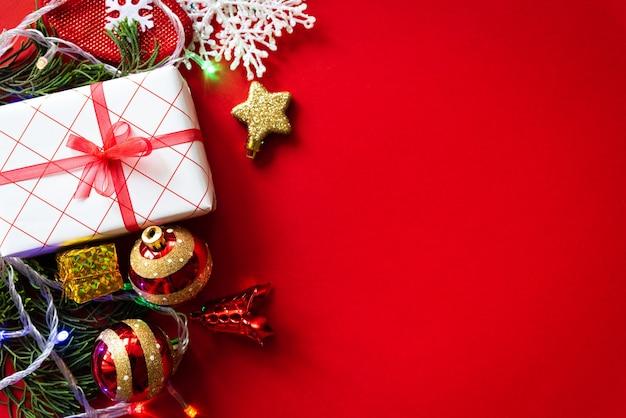 Fond de noël boîte de cadeau de noël avec boule rouge et des pommes de pin sur fond rouge.