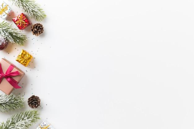 Fond de noël avec boîte-cadeau en pin et paillettes de décoration sur blanc