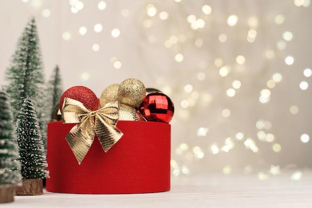 Fond de noël, boîte-cadeau rouge avec un arc d'or sur le fond du bokeh de noël. copier l'espace