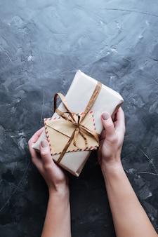 Fond de noël boîtes avec des cadeaux dans les mains sur l'obscurité