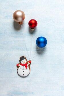 Fond de noël avec un bonhomme de neige et des boules de noël