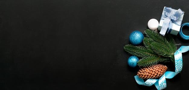 Fond de noël avec des boules bleues et des branches de sapin