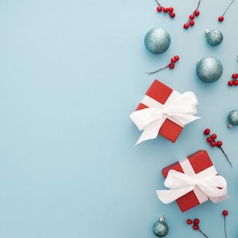Fond de noël avec des boules bleues, des cadeaux rouges et du gui