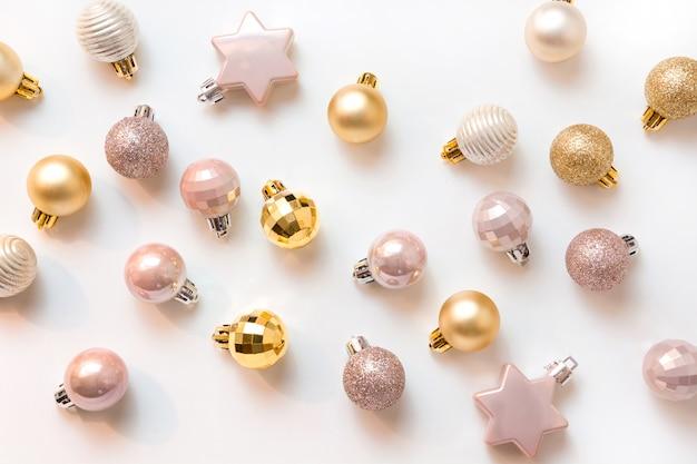 Fond de noël avec des boules de paillettes dorées et roses sur blanc. vue de dessus. motif de noël. nouvel an. carte de voeux.