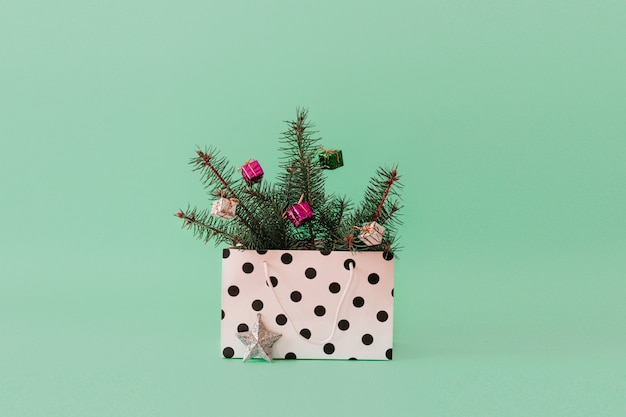 Fond de noël avec des branches d'arbres et boule de boule dans un sac cadeau