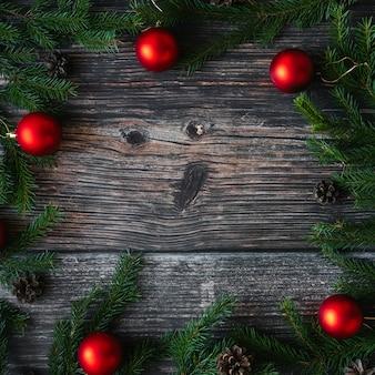 Fond de noël avec des branches de sapin, des boules rouges et des pommes de pin sur bois.