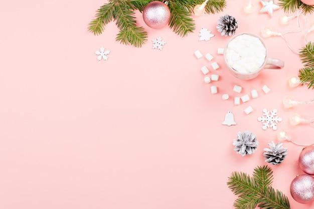 Fond de noël avec des branches de sapin, des coffrets rouges, des décorations, une boisson chaude avec des guimauves sur rose. espace de copie