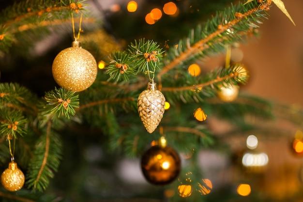Fond de noël avec des branches de sapin, des décorations de noël et un cône de verre doré et des boules jaunes et orange
