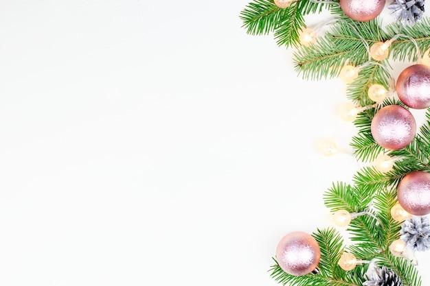 Fond de noël avec des branches de sapin, lumières de noël, décorations roses et beiges, ornements en argent