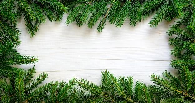 Fond de noël avec des branches de sapin sur planche de bois blanc