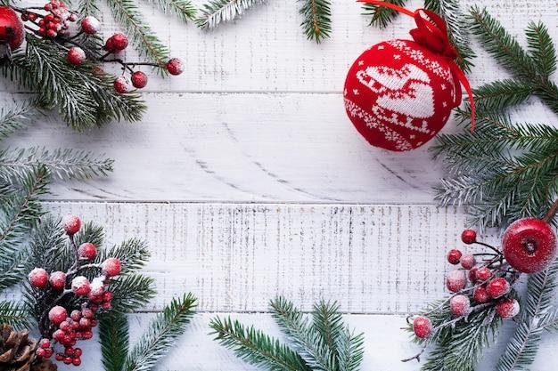 Fond de noël avec des branches de sapin, pommes de pin, boîte-cadeau, oranges séchées, anis étoilé et baies sur la vieille planche de bois blanche. vue de dessus.