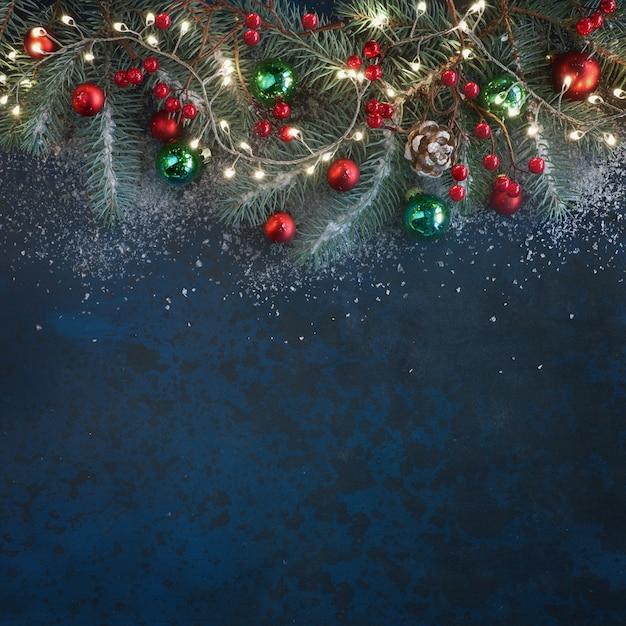 Fond de noël avec des brindilles de sapin, baies rouges, cônes et lumières de noël sombre, copie-espace