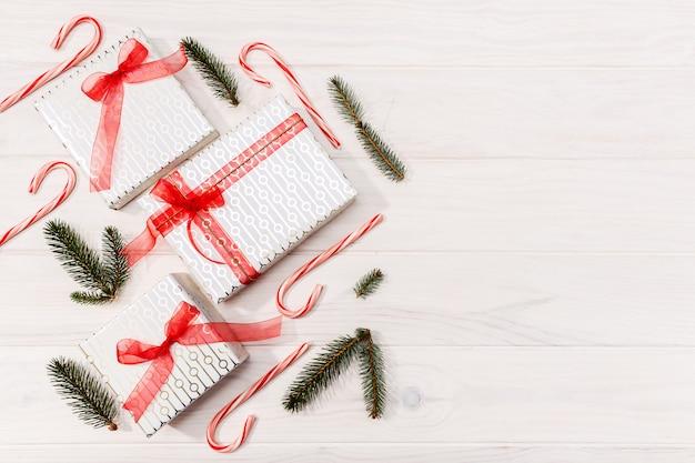 Fond de noël cadeaux, branches de sapin, décorations rouges sur fond en bois blanc. lay plat, vue de dessus, espace de copie